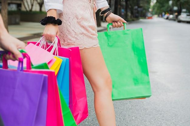 Mulher andando na estrada com sacolas de compras