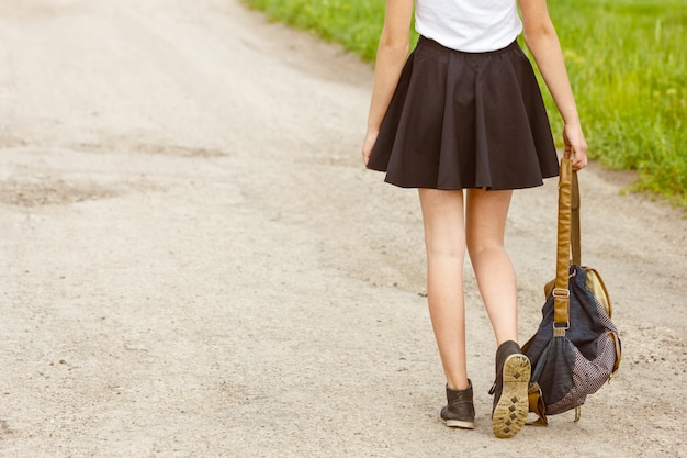 Mulher andando na estrada segurando a mochila na mão