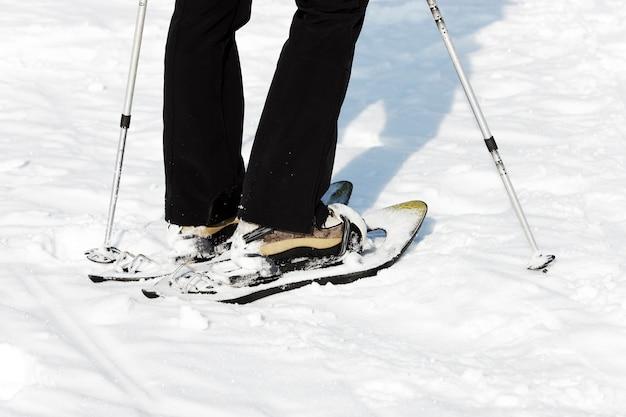 Mulher andando na neve com raquetes