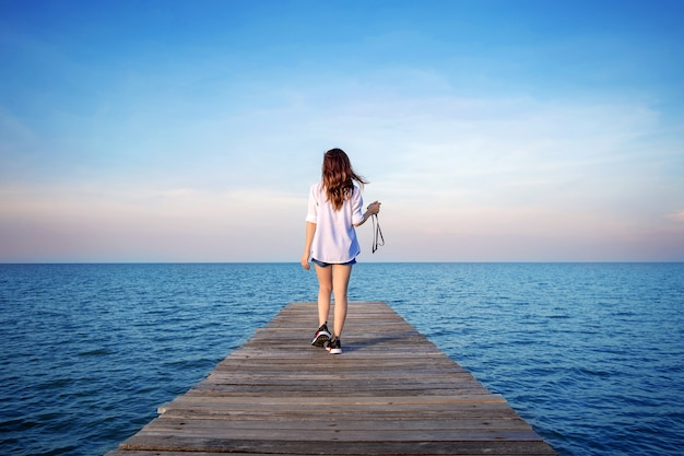 Mulher andando na ponte de madeira estendida para o mar.