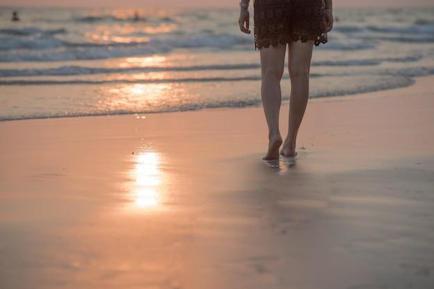 Mulher andando na praia ao pôr do sol.