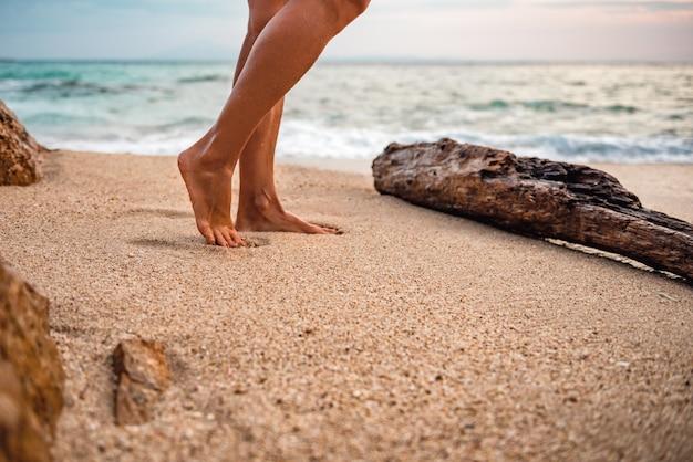 Mulher andando na praia com os pés descalços durante o pôr do sol