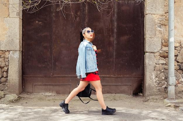 Mulher andando na rua ao lado de uma porta enferrujada