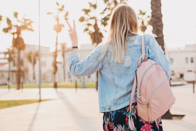 Mulher andando na rua da cidade com uma elegante jaqueta jeans grande e segurando uma mochila de couro rosa