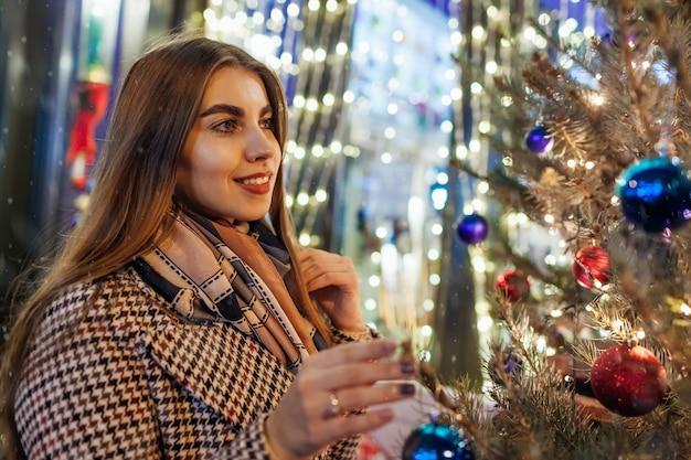 Mulher andando na rua da cidade por árvores de natal decoradas. menina estilosa aproveitando a atmosfera mágica das férias sob a neve que cai