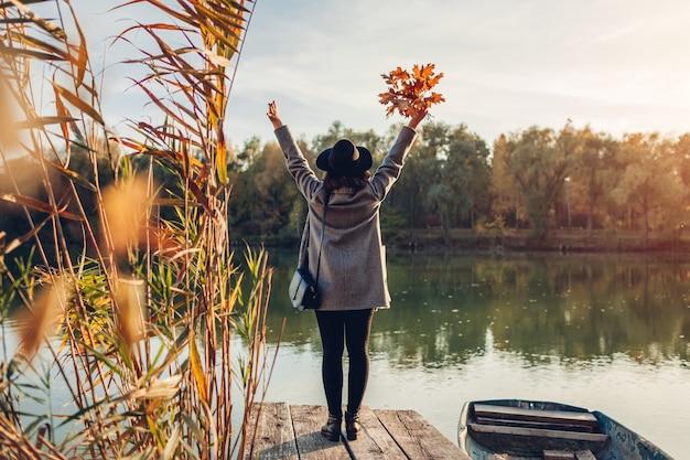 Mulher andando no cais do lago de barco, levantando as mãos e admirando a paisagem de outono. atividades da temporada de outono