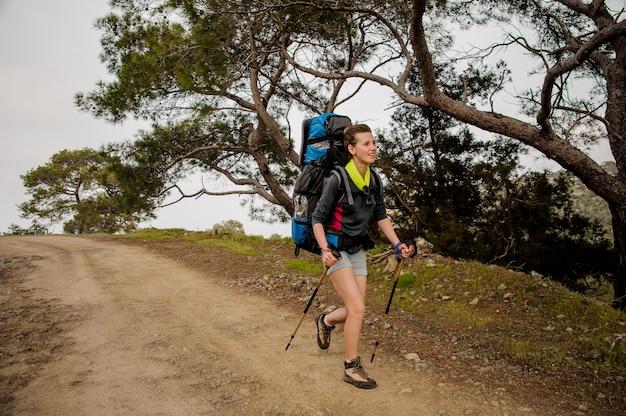 Mulher andando no caminho com mochila de caminhada