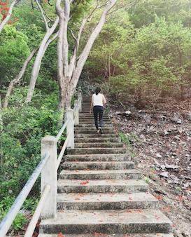 Mulher andando no degrau com fundo de árvore verde com filtro vintage