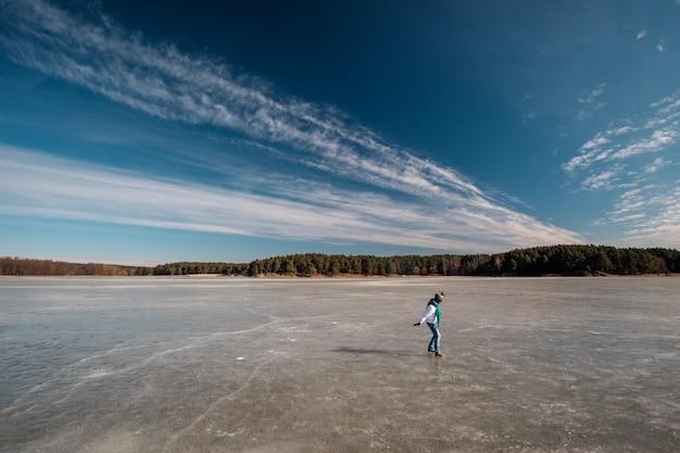 Mulher andando no gelo no lago congelado no inverno