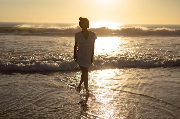 Mulher andando no mar na praia