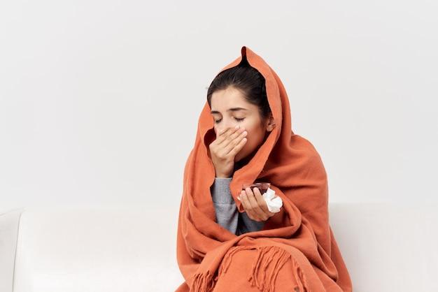 Mulher andando se escondendo atrás de uma manta em casa com uma xícara de chá parece pouco saudável