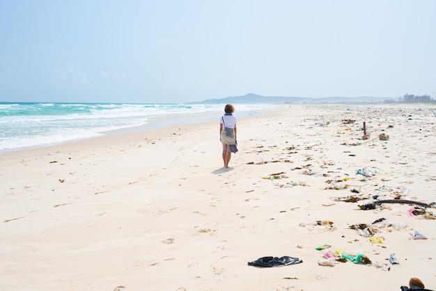 Mulher andando sozinho na praia tropical com plástico de lixo lixo na areia. acenando o problema de poluição da praia no deserto do mar no mar