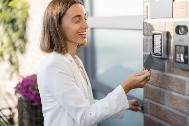 Mulher anexa o cartão ao leitor eletrônico para acessar o apartamento. entrada de cartão, identificação pessoal, acesso sem chave, tecnologias na vida cotidiana