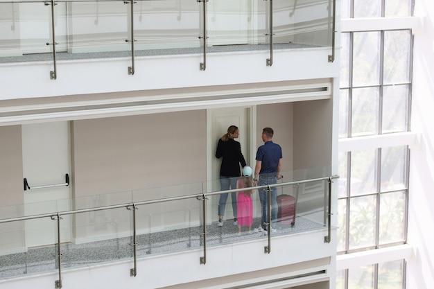 Mulher anfitriã abrindo a porta de um hotel para o homem e sua filha