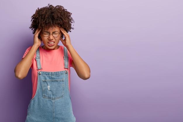 Mulher angustiada de pele escura segura as têmporas, sente dor de cabeça, tenta se concentrar, usa camiseta casual e sarafan jeans