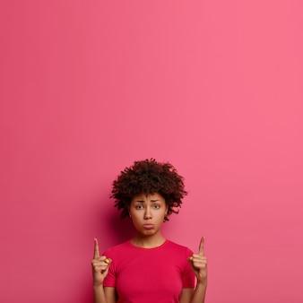 Mulher angustiada e miserável aponta para cima e parece relutante, insatisfeita com os preços, mostra espaço de cópia para anúncio, fica encostada na parede rosa, mostra algo extraordinário