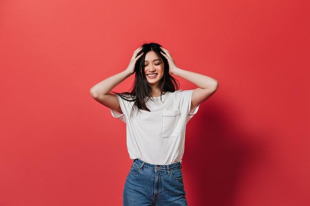 Mulher animada bagunça o cabelo e sorri contra a parede vermelha