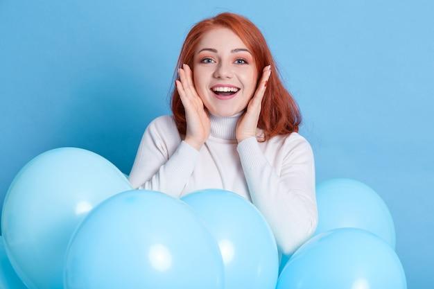 Mulher animada com camisa branca posando contra uma parede azul com as palmas das mãos no rosto