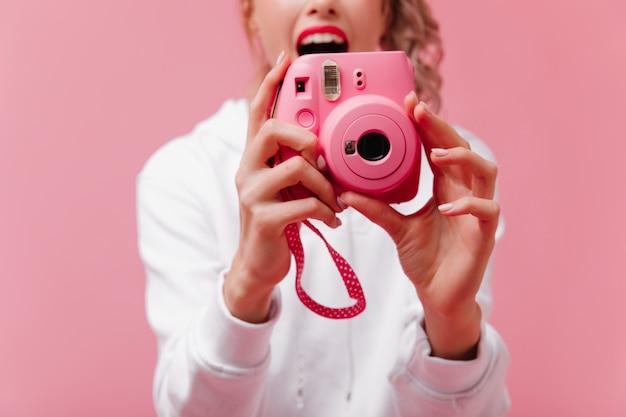 Mulher animada com frente rosa moderna posando no estúdio