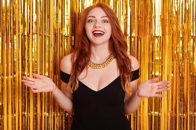 Mulher animada com lindos cabelos ruivos posando contra uma parede decorada com enfeites dourados, espalhando as mãos para o lado, mantendo a boca aberta