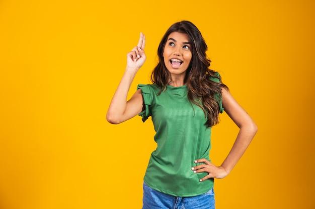 Mulher animada com o dedo apontando no espaço livre para texto. ideia