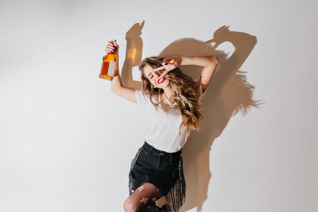 Mulher animada com penteado encaracolado dançando com uma garrafa de conhaque