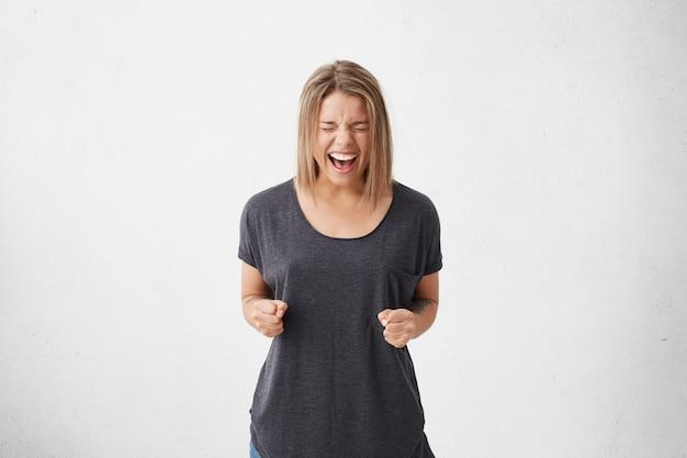 Mulher animada com penteado na moda, fechando os olhos com alegria cerrando os punhos, regozijando-se com seu triunfo e vitória. mulher de sucesso feliz gritando com emoções positivas