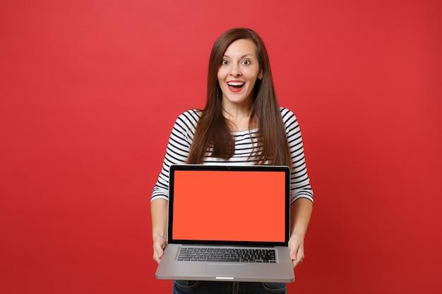 Mulher animada com roupas listradas parecendo surpresa, segurando o computador laptop pc com tela vazia preta em branco, isolada sobre fundo vermelho. emoções sinceras de pessoas, conceito de estilo de vida. simule o espaço da cópia.
