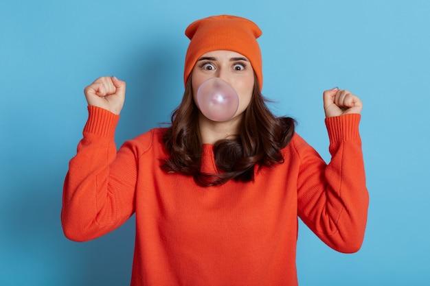 Mulher animada de cabelos escuros sopra bolha de goma de mascar, tem uma expressão de espanto, veste roupas casuais, modelo posa isolada no azul