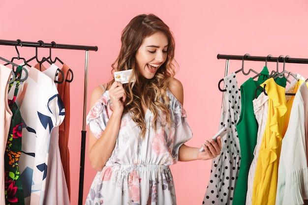 Mulher animada em pé perto do guarda-roupa, segurando um smartphone e um cartão de crédito isolado em rosa