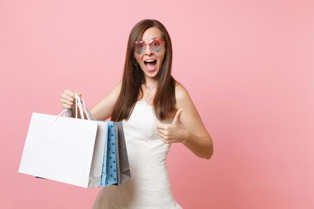 Mulher animada em um vestido branco, óculos em forma de coração aparecendo com o polegar segurando sacolas de pacotes multicoloridos com compras após as compras