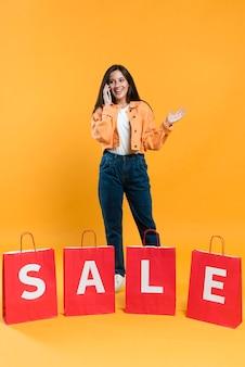 Mulher animada falando ao telefone atrás de sacolas de compras em promoção