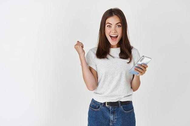 Mulher animada, ganhando o prêmio no telefone, regozijando-se e olhando para a frente feliz, grito de alegria sobre a parede branca.