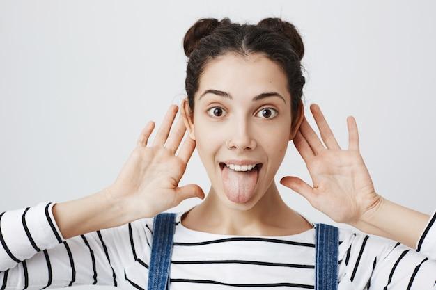 Mulher animada mostra a língua, dá as mãos perto dos ouvidos, escuta