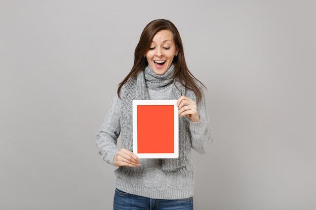 Mulher animada no suéter cinza, lenço segurar computador tablet pc com tela vazia em branco isolada no fundo cinza. tratamento on-line de estilo de vida saudável, consultando o conceito de estação fria. simule o espaço da cópia.