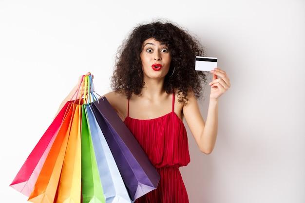 Mulher animada no vestido vermelho, segurando sacolas de compras e mostrando o cartão de crédito de plástico, loja com descontos, fundo branco.