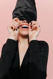 Mulher animada posando com lenço preto na cabeça