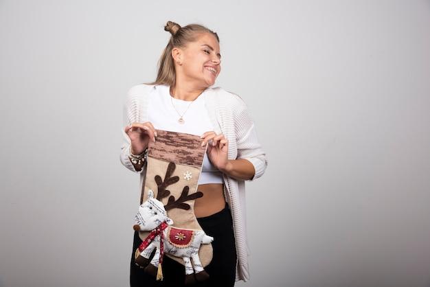 Mulher animada posando com meia de natal em fundo cinza.