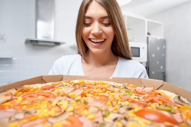 Mulher animada segurando pizza saborosa