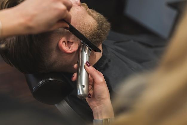 Mulher anônima aparando barba do homem