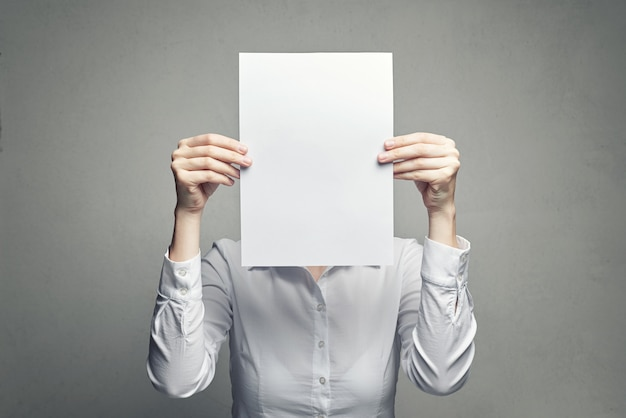 Mulher anônima, cobrindo o rosto com a folha de papel