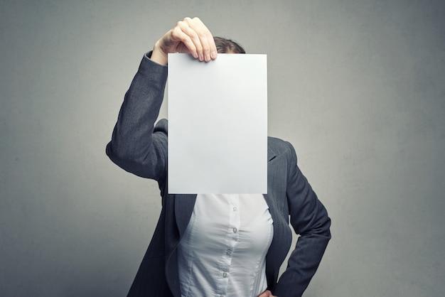 Mulher anônima, cobrindo o rosto com uma folha de papel