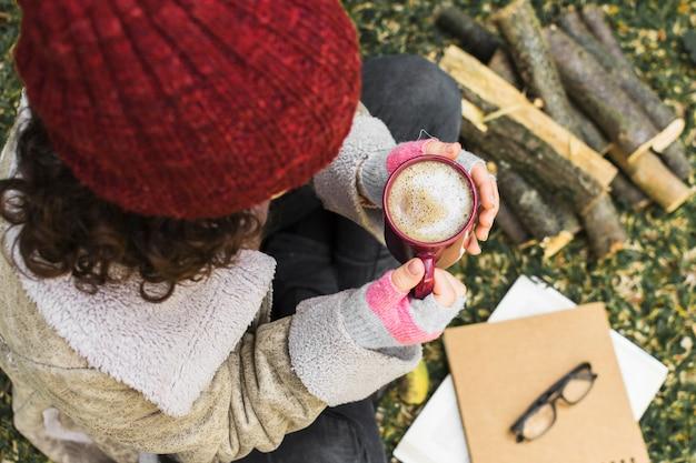 Mulher anônima com café na natureza