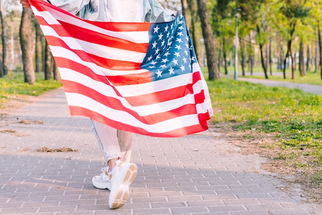 Mulher anônima correndo com a bandeira do eua em quatro de julho