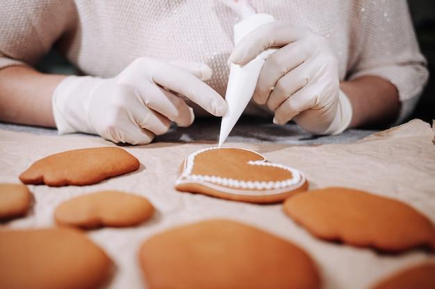 Mulher anônima decorando biscoitos de gengibre caseiros na cozinha