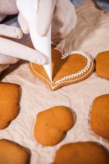 Mulher anônima decorando biscoitos de gengibre feitos em casa na cozinha