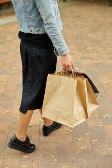 Mulher anônima segurando vários sacos de papel, caminhando ao ar livre no parque