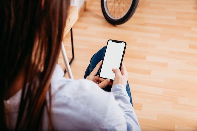 Mulher anônima surfando smartphone em casa