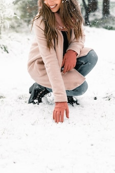 Mulher anônima vestindo roupas quentes, tocando a neve e aproveitando o fim de semana no inverno