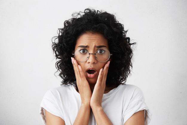 Mulher ansiosa com penteado africano, bochechas macias e grandes olhos escuros